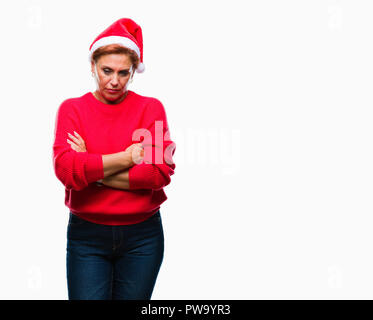 Atrractive senior caucasian redhead woman wearing christmas hat over isolated background skeptic and nervous, disapproving expression on face with cro - Stock Photo