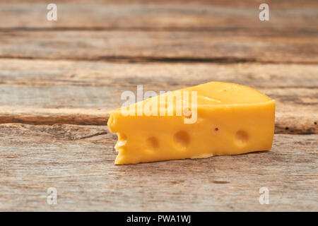 Piece of swiss cheese on wooden background. Dutch cheese with holes on rustic wooden boards. Delicious dairy product. - Stock Photo