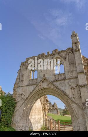 The ruins of Kirkham Priory in North Yorkshire.  The gateway with its carvings largely intact standing under a blue sky. - Stock Photo