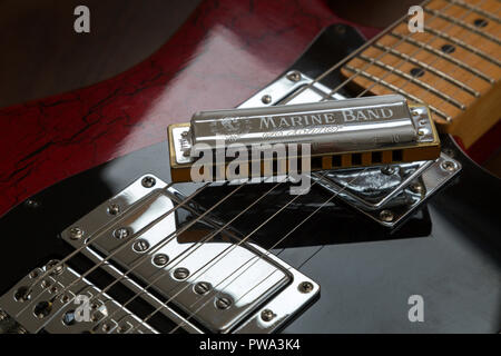 Old electric guitar and harmonica, Hohner Marine Band - Stock Photo