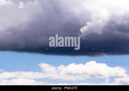 Red arrows flying at Farnborough air show coming out of black clouds - Stock Photo