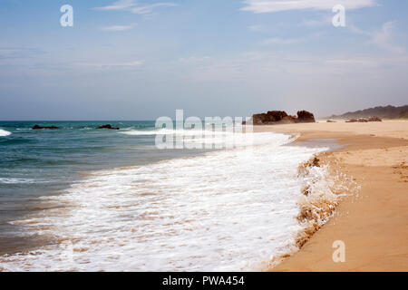 Waves lapping on the shoreline of a sandy beach on a bright day - Stock Photo
