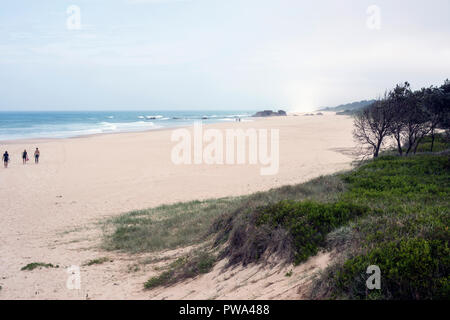 Small figures in distance walking along an idyllic sandy beach toward a bright horizon - Stock Photo