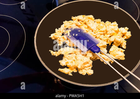 Scrambled eggs in a pan on an induction hob - Stock Photo