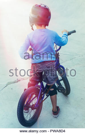 rear view of a boy wearing a black hekmet standing with his bicycle about to start pedaling - Stock Photo