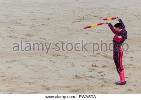 Banderillero holding banderillas in his hands and claiming attention for the bull in a bullfight - Stock Photo