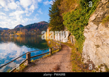 Walking path with a fence along alpine lake Wolfgangsee in austrian Alps. Way from Fuerberg to St. Gilgen, Austria - Stock Photo