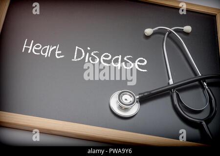 Word Heart Disease written in chalk on a blackboard black next to a stethoscope, conceptual image - Stock Photo