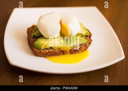 American breakfast. avocado sandwich and poached eggs on rye bread. - Stock Photo
