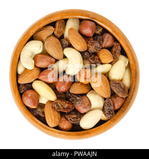 Nuts and raisins in wooden bowl. Snack mix of dried almonds, hazelnuts, cashews and raisins. Trail mix. Edible, raw, organic and vegan. - Stock Photo
