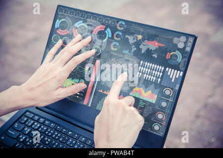 Businesswoman hand using advance technology computer touch screen business information data chart outdoor for decision support system - Stock Photo