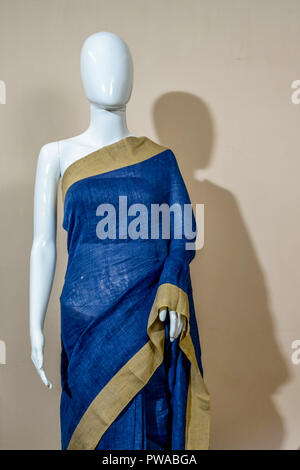 A traditional indian silk saree displayed for sale. Selective focus on model face - Stock Photo