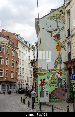 Brussels, Belgium - April 17 :  A man walks past of a fresco of people sitting on trees painted on the walls of a building at Brussels, Belgium, Europ - Stock Photo