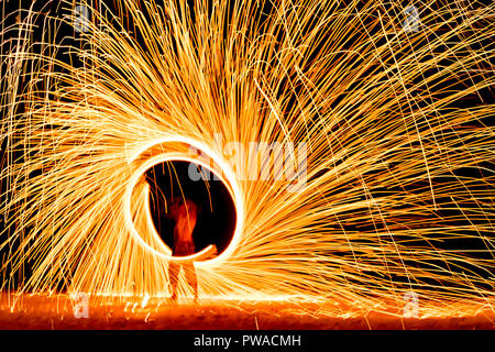 fire dance on beach near the sea , the east coast of thailand - Stock Photo