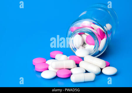 Glass jar with scattered white and pink pills on a blue background. - Stock Photo