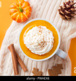 Pumpkin latte with spices. Boozy cocktail with whipped cream on top on knitted scarf. Orange background - Stock Photo