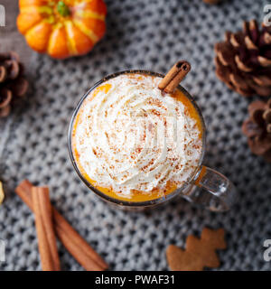 Pumpkin latte with spices and whipped cream. Grey background. Close up. Top view - Stock Photo