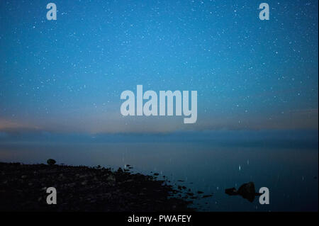Starry night at rocky lake shore. Fog over water in horizon. - Stock Photo
