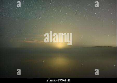 Starry sky above misty lake. City light pollution in horizon. - Stock Photo