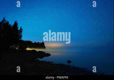 Starry night at lake shore. Fog over water in horizon. - Stock Photo