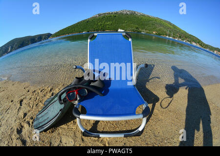 Fisheye landscape with beach chair, snorkeling mask and fins in foreground in strong morning light, Porto Koufo, Sithonia, Greece - Stock Photo