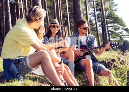 Group of friends partying and listening to music at sunset - Stock Photo