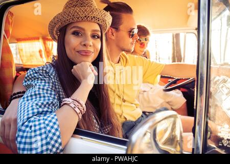Enjoying great roadtrip with friends. Group of cheerful young people having fun while sitting inside of minivan. - Stock Photo