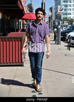 A handsome, casual young man walking past a sidewalk cafe in a small beach town. - Stock Photo