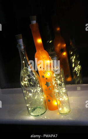 Christmas string LED lights in bottles with reflection in window - Stock Photo