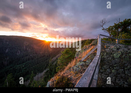 Dramatic sunset in the Harz mountains. Impressive light mood of the landscape with cliffs - Stock Photo