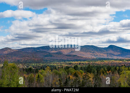 An autumn view of Adirondack Mountains looking east from Indian Lake in New York, USA with blue sky and white clouds casting shadows on the mountains. - Stock Photo