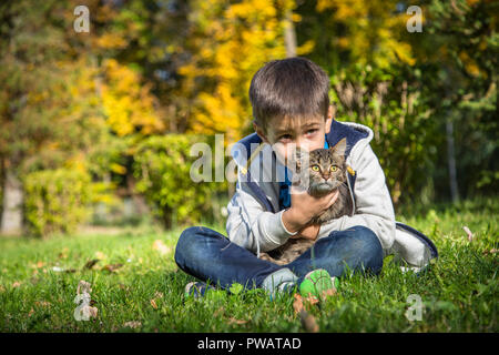 Happy little boy in the autumn park with pet kitten.