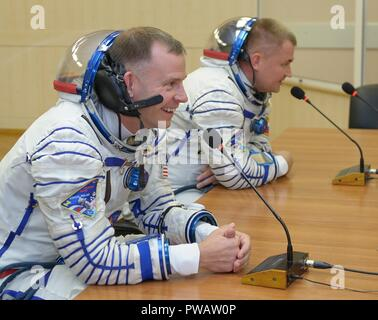 Expedition 57 Flight Engineer Nick Hague of NASA, left, and Flight Engineer Alexey Ovchinin of Roscosmos talk with their families after having their Sokol suits pressure checked ahead of their launch on a Soyuz rocket at the Baikonur Cosmodrome October 11, 2018 in Baikonur, Kazakhstan. Shortly after lift off the rocket malfunctioned en route to the International Space Station and aborted forcing an emergency landing in Kazakhstan. The crew members have been picked up by search and rescue and are reportedly in good condition. - Stock Photo