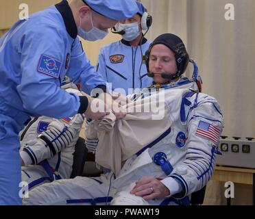 Expedition 57 Flight Engineer Nick Hague of NASA is assisted with his Sokol suit ahead of his launch on a Soyuz rocket with Flight Engineer Alexey Ovchinin of Roscosmos, at the Baikonur Cosmodrome October 11, 2018 in Baikonur, Kazakhstan. Shortly after lift off the rocket malfunctioned en route to the International Space Station and aborted forcing an emergency landing in Kazakhstan. The crew members have been picked up by search and rescue and are reportedly in good condition. - Stock Photo