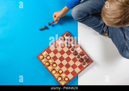 Kid sitting and learning to play chess game. Top view - Stock Photo