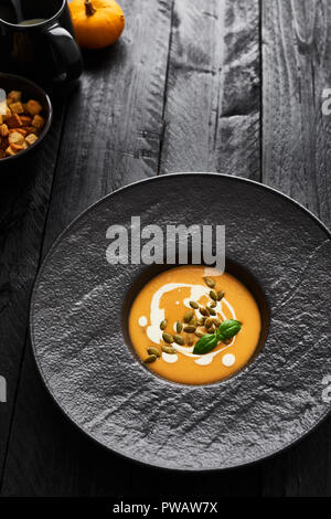 Pumpkin and carrot soup with pumpkin seeds, cream and basil in black modern plate on dark wooden table with copy space. Dark modern style. Top view. - Stock Photo