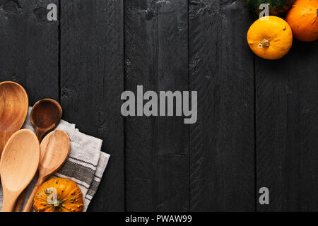 Autumn vegetables cooking preparation. Top view of pumpkins, wooden spoons and dishtowel on black wooden background with copy space. - Stock Photo