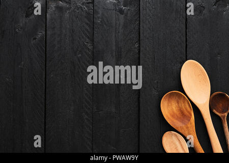 Wooden spoons on black wooden background with copy space. Top view of various types of wooden spoons on dark wooden background. - Stock Photo