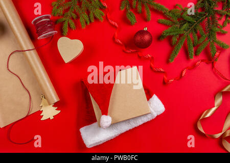 Preparing for Christmas: wrapping paper, decorations and present gift box with Santa's hat on red background - Stock Photo