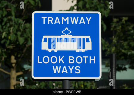 A sign reads 'Tramway Look Both Ways' in St Peter's square in Manchester, referring to the city's Metrolink system. - Stock Photo