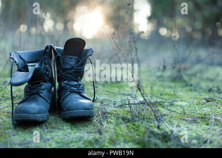 Close up of vintage pair of walking boots on boulder grassland background. Hard travel concept - Stock Photo