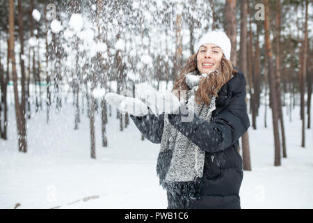 Beautiful girl in a hat and winter clothes throws up snow and enjoys good weather. Positive emotion - Stock Photo