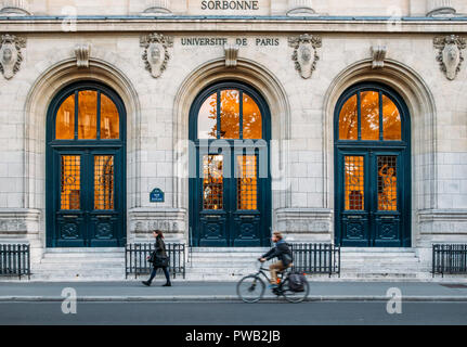 Paris, France - Oct 13, 2018: Pedestrian and cyclist with outside facade of the prestigious University Sorbonne in Paris, France - Stock Photo