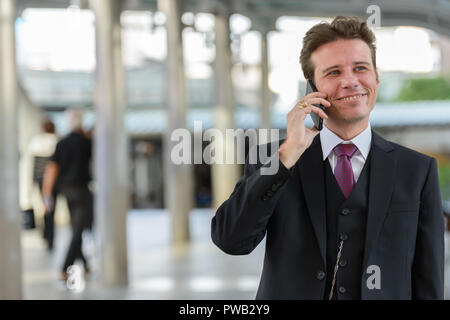 Happy thoughtful businessman smiling and talking on mobile phone - Stock Photo