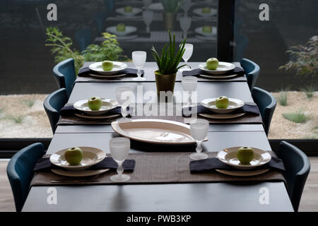 Overhead view of a long dining table set with six plates - Stock Photo