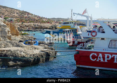 Excursion boats moored to the rocks in Blue Lagoon, Comino Island, Malta, to allow their holidaymakers to swim and dive in the crystal-clear waters - Stock Photo