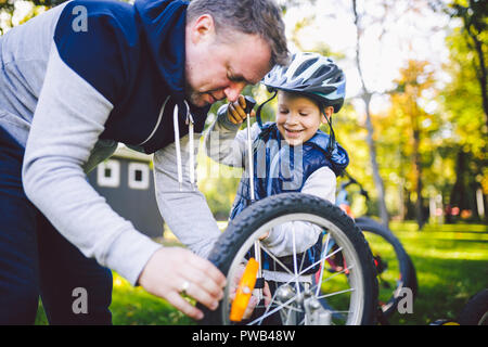 Father's day Caucasian dad and 5 year old son in the backyard near the house on the green grass on the lawn repairing a bicycle, pumping a bicycle whe - Stock Photo