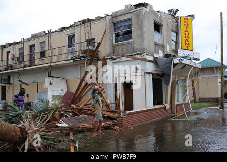 Panama City, FLORIDAY, USA. 10th Oct, 2018. People walk through the wreckage of a building after Hurricane Michael passed over in Panama City, Florida USA on October 10, 2018. Hurricane Michael made landfall in the Florida panhandle as a Category 4 hurricane. Credit: Dan Anderson/ZUMA Wire/Alamy Live News - Stock Photo