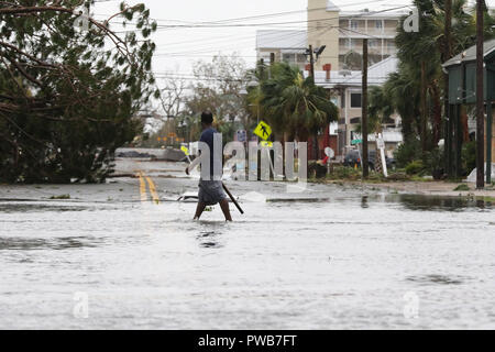 Panama City, FLORIDAY, USA. 10th Oct, 2018. A man walks through a flooded street after Hurricane Michael passed in Panama City, Florida USA on October 10, 2018. Hurricane Michael made landfall in the Florida panhandle as a Category 4 hurricane. Credit: Dan Anderson/ZUMA Wire/Alamy Live News - Stock Photo
