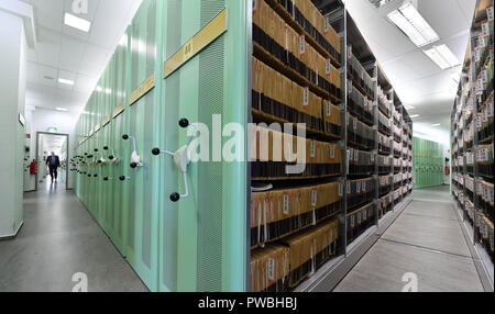 15 October 2018, Thuringia, Jena: An employee walks along the shelves in the trademark archive of the Jena office of the German Patent and Trademark Office. The East German branch of the Patent Office in Munich has been in existence for 20 years. The settlement was decided by the Federalism Commission in 1992. Since then, the employees have been responsible for design protection and, together with Munich, for trademark protection. The branch currently employs a total of 229 civil servants and employees. Photo: Martin Schutt/dpa-Zentralbild/dpa - Stock Photo